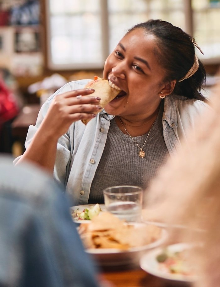 Woman happily eating a taco