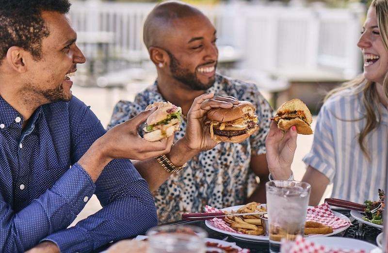 Two men and a woman enjoying burgers